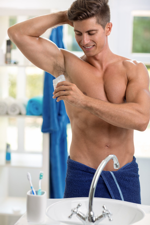 Smiling man front of mirror using roll-on antiperspirant Stock Photo