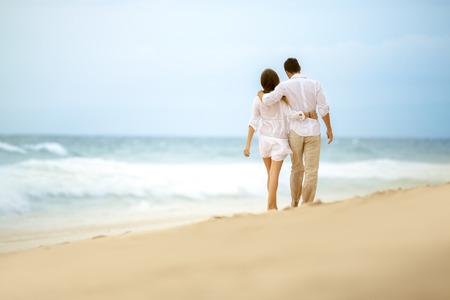 romântico: casal caminhando na praia, abraçando pares do amor