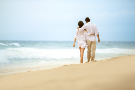 parejas romanticas: pareja caminando en la playa, abrazando la pareja el amor Foto de archivo