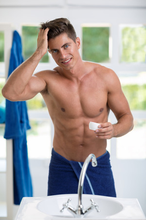 body grooming: Male front mirror making hairstyle,  young smiling man puts on the hair hardener
