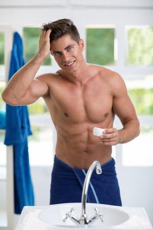 uomini belli: Maschio fronte specchio facendo acconciatura, giovane uomo sorridente mette sul catalizzatore capelli