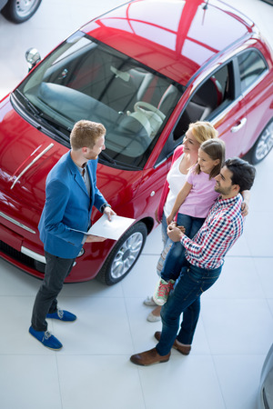 auto dealership: family with car dealer in car dealership saloon