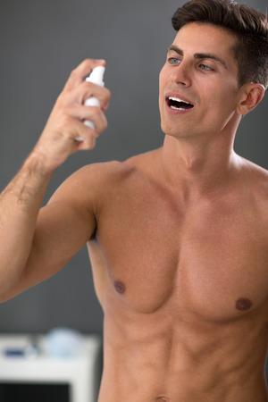 pulverizador: hombre guapo joven que usa el spray aliento de menta