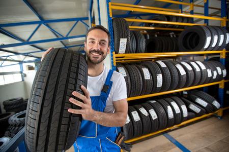 tienda de ropa: sonriendo mec�nico de autom�viles que lleva los neum�ticos en la tienda de neum�ticos