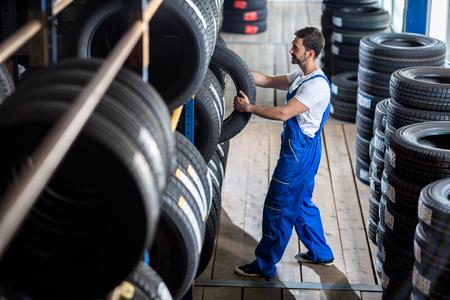 자동차 정비공은 타이어 가게에서 자동차 타이어를 선택 스톡 콘텐츠