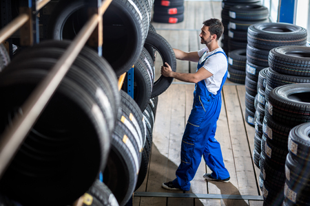 car salesperson: Auto mechanic  choose tire for car at a tire store