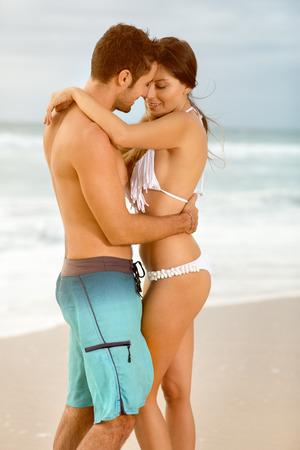 femme romantique: vacances d'�t�, les gens, amour, Voyage et rencontres concept - couple heureux embrassant sur le coucher du soleil plage Banque d'images
