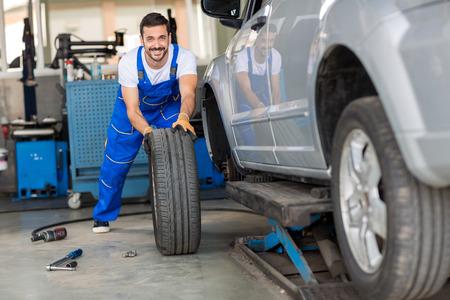 mechanic hands in blue uniform pushing a black tyre in a workshop Archivio Fotografico