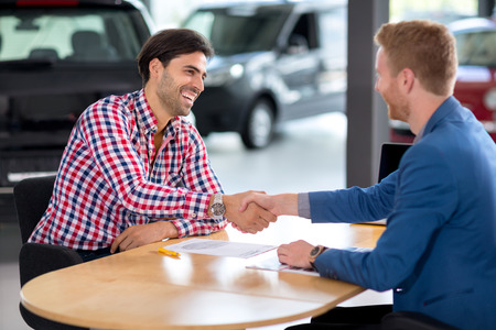 Happy man an buying a car in dealership they are shaking hands to close the deal