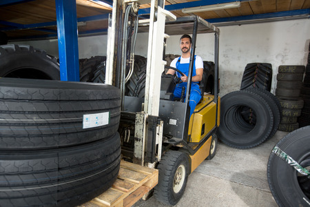 forklifts: Large modern garage with forklifts and stack of car tires Stock Photo