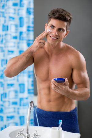 cuerpo hombre: Hombre atractivo de la asistencia sanitaria que mira en espejo pone en la crema