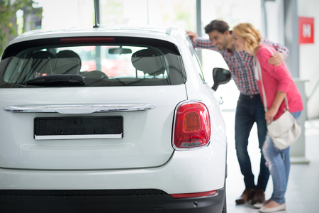 car dealership: Beautiful young couple standing at the car dealership and making their decision, concept buy  new car Stock Photo