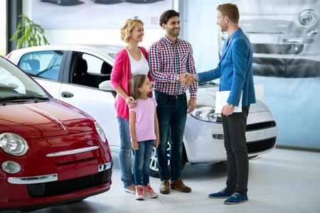 carro supermercado: La familia feliz comprar nuevo coche, concesionario de automóviles apretón de manos con el papá felicitó a la familia en un coche nuevo Foto de archivo