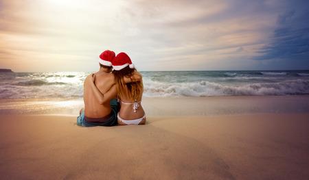 pareja abrazada: Abrazar pareja en la playa mirando la puesta del sol con sombrero de Navidad Foto de archivo