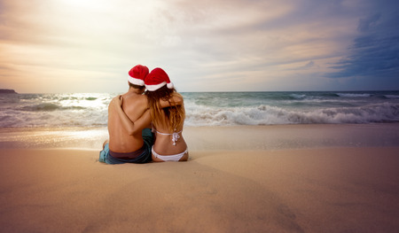 christmas hat: Embracing couple on beach looking sunset with Christmas hat Stock Photo