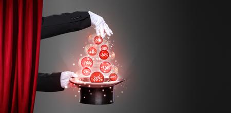 Handen van de goochelaar en hoge hoed op het podium, concept Kerstmis kortingen Stockfoto