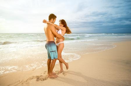 enamorados besandose: Joven pareja cariñosa en la playa Foto de archivo