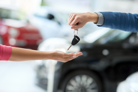 Close up of car dealer giving keys to woman 스톡 콘텐츠
