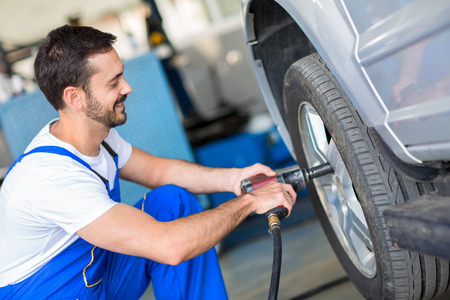 impact wrench: Mechanic changing wheel on car with impact wrench Stock Photo
