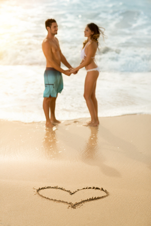 happy couple: romantic happy couple with draw heart on sandy beach Stock Photo