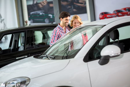 car dealership: Couple in  car dealership saloon looking for a new car Stock Photo