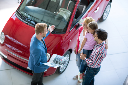 saloon: Young family with car agent in  the car dealership  saloon