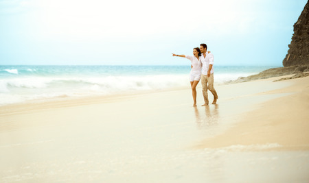 Young couple walking on a sandy beach along a coastline