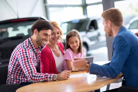 Pc のタブレットを探して車屋で若い家族 写真素材