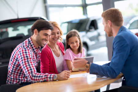 new automobiles: Young family  in car dealership looking in pc tablet