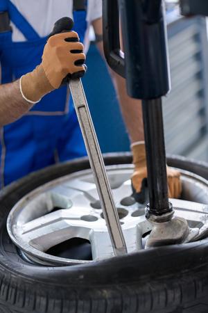 zastąpić: repairman with installer replace tire on wheel  in workshop