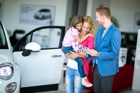 car sales: Young woman with child in  car dealership looking at brochure with salesman