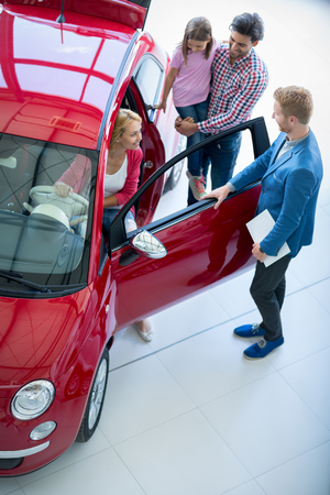 auto dealership: Young family chooses to buy a car in the car dealership  saloon Stock Photo
