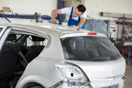sandblasting: Car painter polishes scratches on car in service