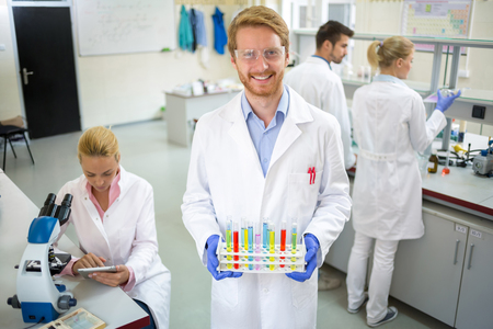 laboratory research: Smiling chemical technician hold colorful test tubes