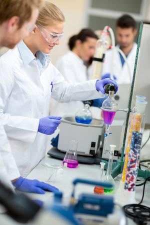 Cute female chemist doing experiment mixing liquids in chemical lab Archivio Fotografico