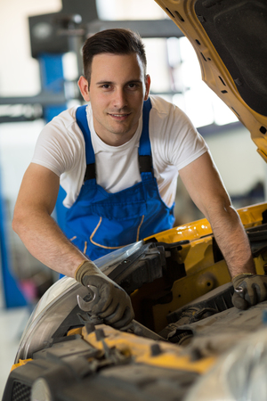 engine bonnet: portrait mechanic working on engine on car