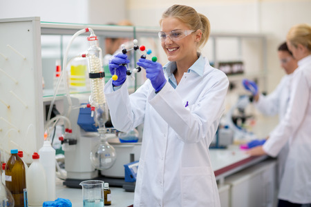 molecular model: Young cheerful female chemist hold molecular model in lab