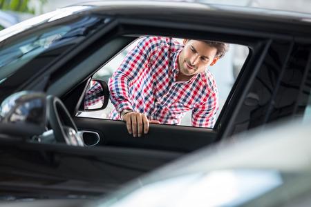 Hombre joven feliz que elige para comprar un coche en el concesionario de coches berlina Foto de archivo - 47502772