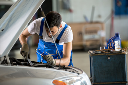 bonnet up: Auto mechanic working under the hood in garage Stock Photo