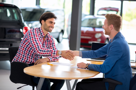 auto dealership: Man at a car dealership buying an auto, car agent handshake with his client