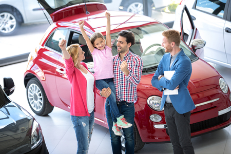 Happy family at the dealer buying a new car, excited with hands up