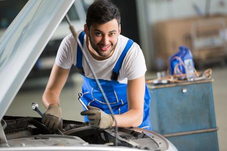 mecanico: sonriendo mec�nico que trabaja en el motor en el garaje