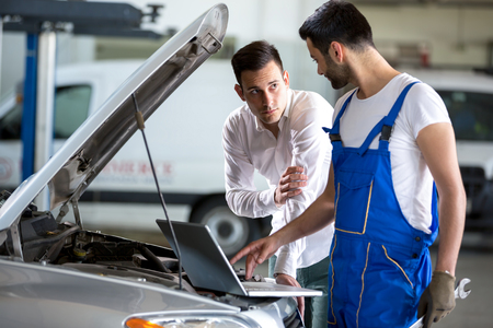 diagnostic tool: mechanic working on laptop computer with customer