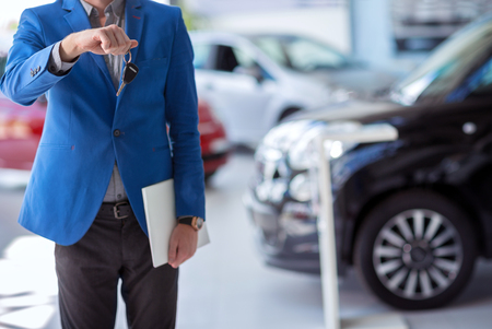 automobile dealership: car agent  in car dealership saloon holding car key in front of him Stock Photo
