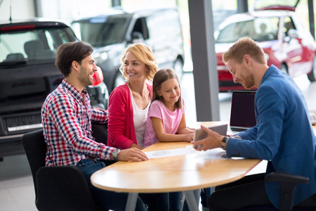 salesperson: Car salesperson demonstrating new automobile to young family