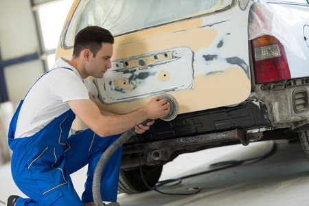sandblasting: Car painter polishes body part for paint