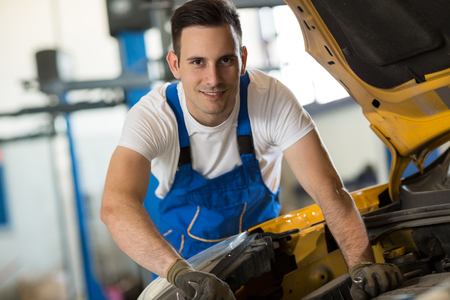bonnet up: Smiling mechanic working on engine on car Stock Photo