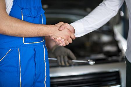 stretta di mano: ragazzi stretta di mano in servizio di riparazione auto Archivio Fotografico