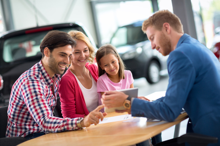 Happy family in car dealership choosing their new car, friendly car agent helping