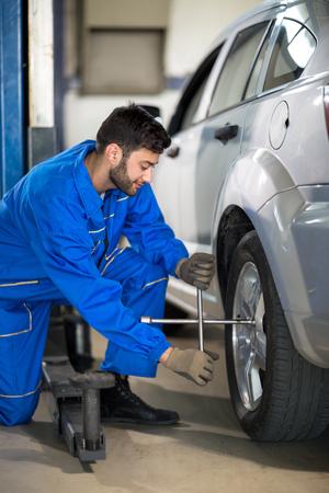 impact wrench: Uniform mechanic working on tyre in garage